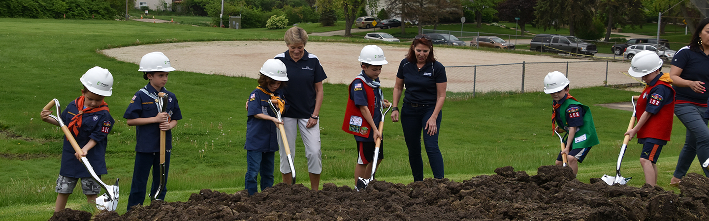 students digging at the new school groundbreaking