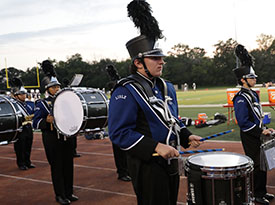 Drummers in the marching band perform at a football game.