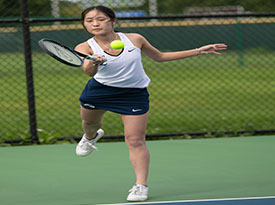LHS tennis player hits the ball.