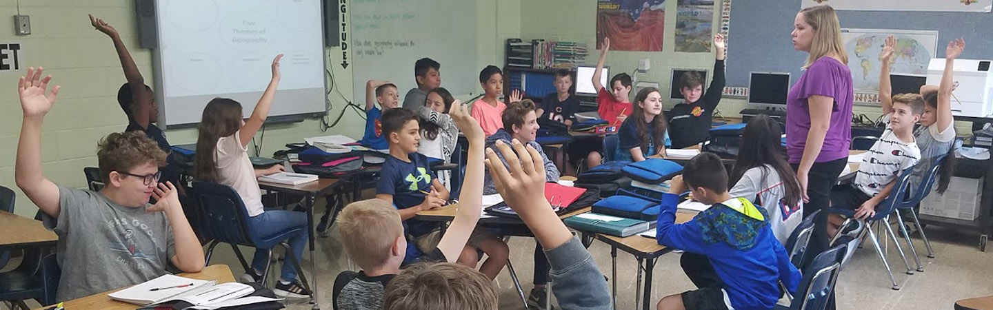7th-grade social studies students raising their hands in class