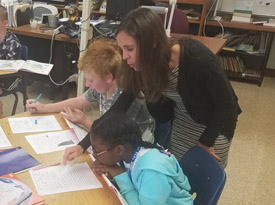 Mrs. Pilon working with her sixth-grade social studies students
