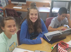 8th-grade literature students working on Chromebooks, smiling at camera
