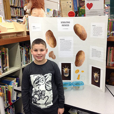 Schiesher student stands in front of his science fair project.