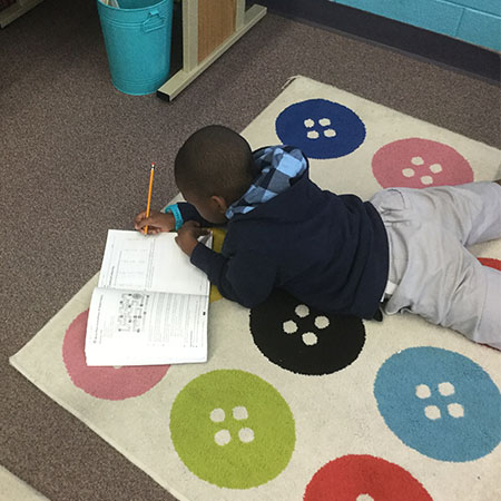 Schiesher student works independently on the carpet