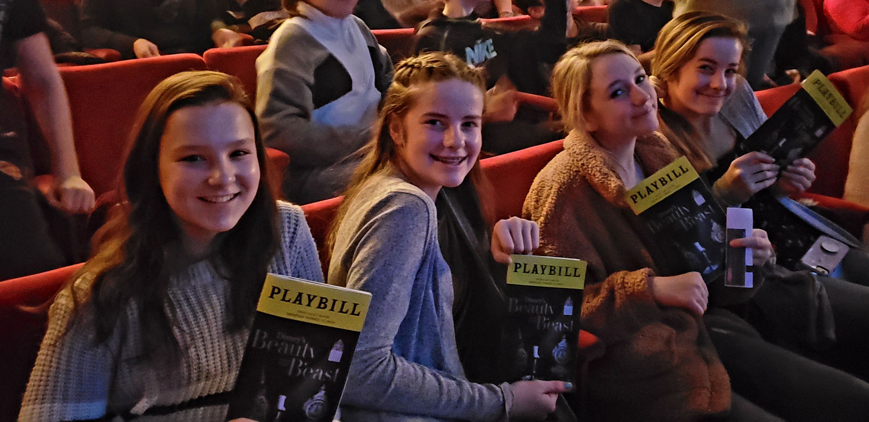 students holding playbills in the theater