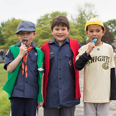 three boys eating ice cream treats, two in cub scouts uniforms