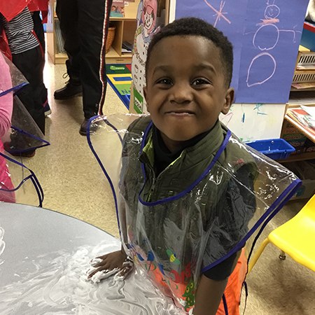 Pre-Kindergarten students works with shaving cream on a table