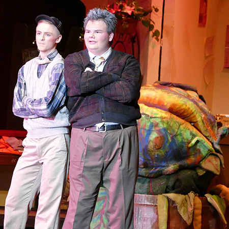 Two students stand in front of Seymore in musical Little Shop of Horrors