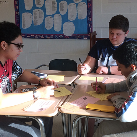 Three Lisle High School students work in a group in class