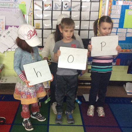 three kindergarten students hold up boards with h-o-p