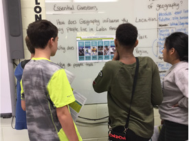 Science class circles up around student led discussion and SmartBoard