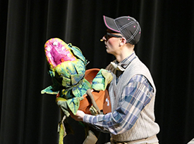 Lisle High School musical Little Shop of Horrors character holds baby Seymore