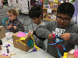 Three Tate Woods students cut paper to create geometric shapes